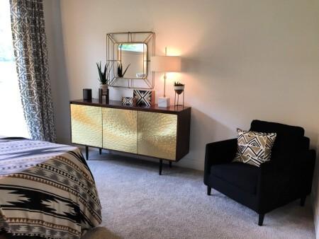 Mid Century Modern Bedroom featuring mirror, gold hammered dresser, & blue velvet chair