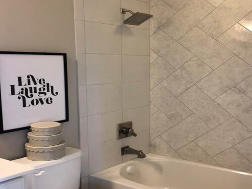 grey bathroom with grey & white marbled chevron wall bath tile